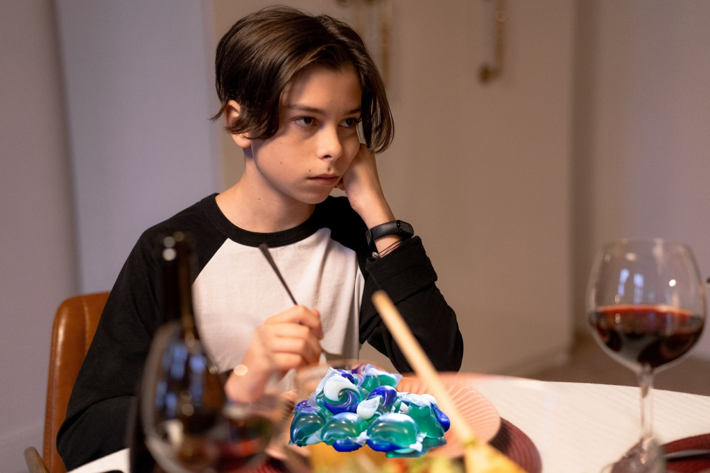 A sulking teen glares at his parents with a plate of equate-brand tide pods on his dinner plate.